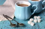 Cups of coffee with sugar and napkin on wooden table