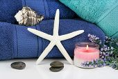 Fluffy Towels, A White Starfish,  Spa Stones, Candles And Flowers In A Spa Setting. poster