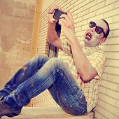 a scary zombie taking a selfie of himself with a smartphone, with a retro effect