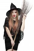 Woman winking eye in witch costume with a broom