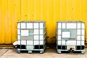 White IBC container in front of a yellow cargo container