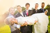 picture of mans-best-friend  - Outdoor portrait of young groom with his friends holding beautiful bride - JPG