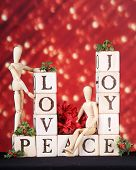 Love, joy and Peace spelled out in rustic Alphabet blocks.  They're adorned by two mannequins, holly and a small bouquet of red poinsettias on a red background of festive lights.