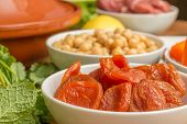 image of tagine  - Ingredients for a Moroccan tagine dish with dried apricots chick peas lamb mint and lemon - JPG