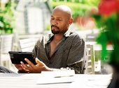 mature african man using smart phone outdoors
