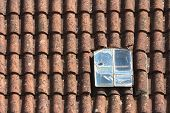 Old Broken Dormer Window In The Red Tiled Roof