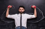 Serious businessman with dumbbells and painted muscular arms on chalkboard