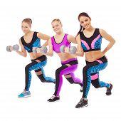 Smiling female athletes posing with dumbbells