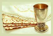 stock photo of passover  - the symbols of the feast of the Passover matzah a Cup with wine and font in Hebrew white cloth with embroidery white background isolated - JPG