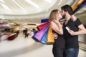Happy Kissing Couple With Shopping Bags In The Mall
