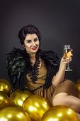 Happy Fashion Woman Drinking Champagne, Dressed In A Gold Dress And Feathers Collar, Surrounded With