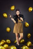 Happy Fashion Woman Holding Fireworks Dressed In A Gold Dress And Feathers Collar, Surrounded With Y