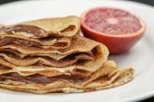 thin crepes or blinis with chocolate cream on plate