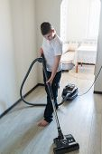 Kid using vacuum cleaner in  house