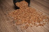 Buckwheat Sprinkling From A Black Bowl On The Wooden Table Background