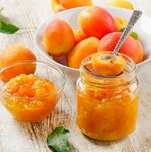 stock photo of apricot  - Fresh apricots jam on a wooden table - JPG