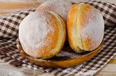 Sweet Donuts With Powdered Sugar On A Wooden Plate.