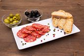 Antipasto of salami and olives on wood