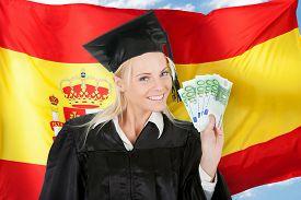 stock photo of spanish money  - Female Graduate Student Holding Money In Front Of Spanish Flag - JPG