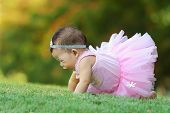 stock photo of crawling  - Asian baby wearing a pink dress was crawling in the grass - JPG