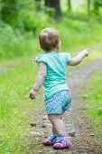 picture of girl walking away  - Cute Little girl walking away on the road ahead looking back - JPG