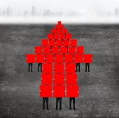 picture of compose  - Red arrow up shape composed of boards holding by men with gray concrete floor background - JPG