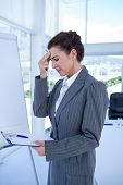 picture of unnerving  - Irritated businesswoman looking at clipboard in medical office - JPG