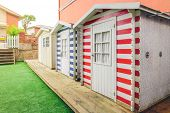 pic of beach hut  - Row of three colorful beach striped huts in a home garden - JPG