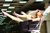 image of trolley  - One young beautiful fashion girl in black dress sitting in shopping trolley indoor on store backdrop horizontal picture - JPG