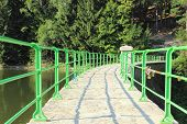 picture of dam  - Green bridge and dam water on a mountain trail