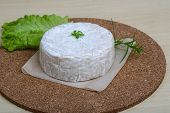 foto of brie cheese  - Brie cheese with salad leaves on the wood background - JPG