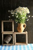 stock photo of pitcher  - Beautiful bouquet of daisies in pitcher with twine on wooden background - JPG