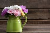 stock photo of pitcher  - Beautiful chrysanthemums in pitcher on wooden background - JPG