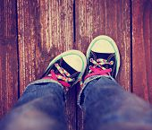 stock photo of pink shoes  - a wide angle photo of a pair shoes with pink shoe laces on a vintage wooden background pointing one toe in toned with a retro vintage instagram effect app  - JPG