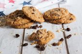stock photo of baked raisin cookies  - Oatmeal raisin cookies on a table with a printed tea towel in the background - JPG