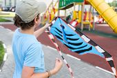 stock photo of post-teen  - boy with a kite in his hands - JPG