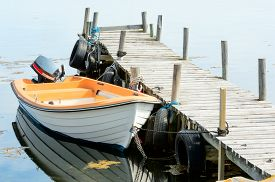 foto of outboard  - Small outboard motor boat secured by a wooden bridge with car tires as fenders - JPG