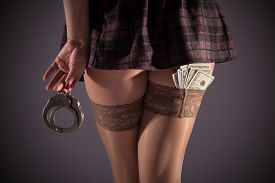 stock photo of handcuff  - Female prostitution violation of the law steel handcuffs fan of banknotes payment for services selling body for money immorality youth feet in nylon stockings steel handcuffs - JPG