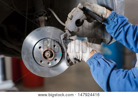 poster of Brand new brake disc on car in a garage. Auto mechanic repairing a car.