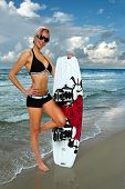 Beautiful girl with wakeboard on the shore of beach