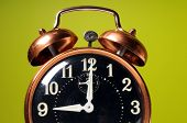 Close up of vintage alarm clock over a green background