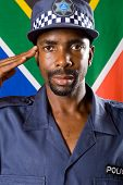 south africa policeman saluting, background is south african flag