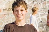 portrait of a young teen boy, background is his friends playing skateboard
