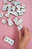 senior woman hand holding a piece of mahjong tile