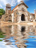 Old church in colonial town. Reflection in water.