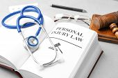 Book With Words Personal Injury Law And Stethoscope On Table poster