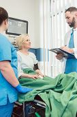 Doctor and nurse talking to patient in recovery room of hospital after she woke up from operation  poster