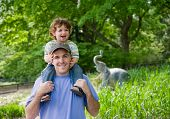 Dad Carrying Toddler On Shoulders At Zoo.