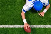 Overhead photo of an American football player making a one handed touchdown. The uniform he's wearin