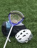 A Purple Goalie Lacrosse Stick Is Resting On An Athletes Gear Bag With A Helmet Next To Both On The  poster